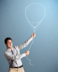 Young man holding balloon drawing