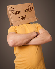 Young man gesturing with a cardboard box on his head with evil f