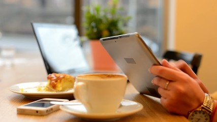 woman works on tablet in cafe - urban street in background