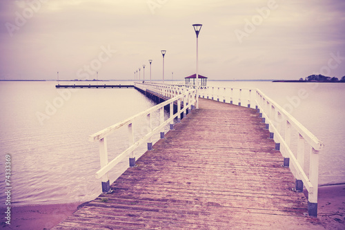 Vintage retro filtered wooden pier at sunset. - 74333369