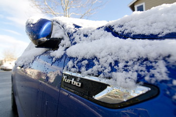 Close-up of a parked sport car covered by snow