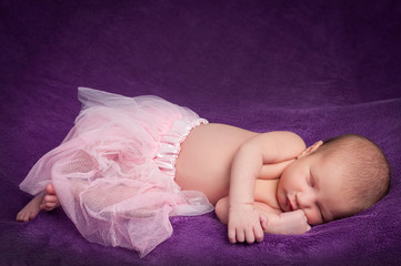 sleeping newborn on purple background
