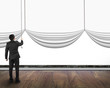 businessman pulling open blank curtain with empty white backgrou