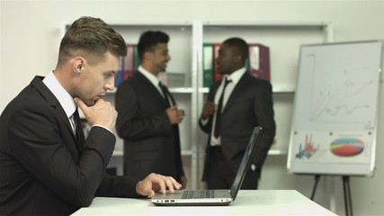 The manager work on the laptop and businessmen discuss