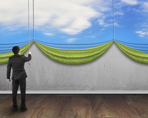 businessman pulling open natural sky curtain covered concrete wa