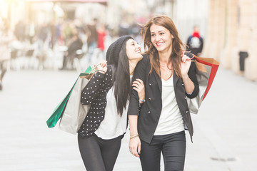 Happy Women Walking in the City with Shopping Bags