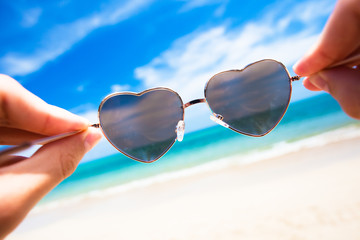 close up of heart-shaped sunglasses. sunny beach in thailand