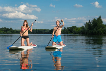 Attractive couple knees on stand up paddle board in the lake