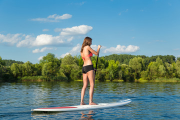 Young attractive woman on stand up paddle board in the lake, SUP