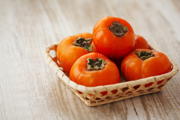 persimmon in a wicker basket on a light wooden background