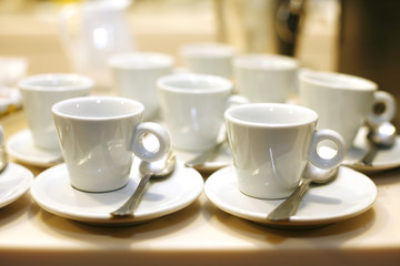 white empty coffee cups and saucers