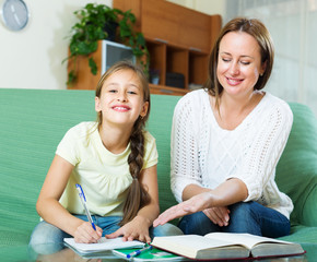 Happy schoolgirl and mother together doing homework