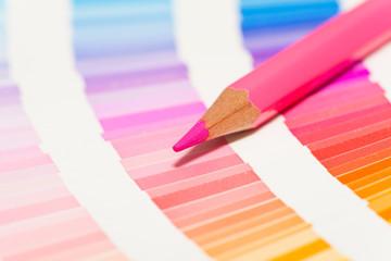 crayons de couleur rose sur un nuancier de teintes rose bleu