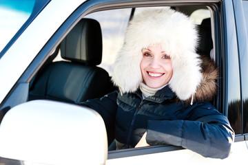 Pretty woman in white fur hat in a car