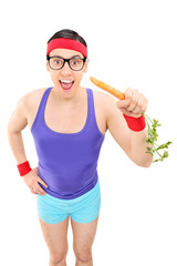 Excited man in sportswear eating a carrot