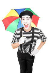 Excited mime artist holding a colorful umbrella