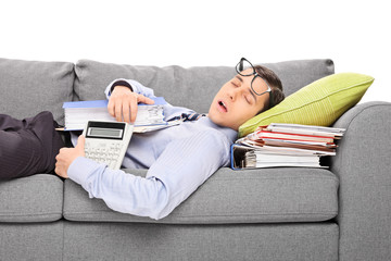 Male accountant sleeping on a pile of folders