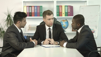 The businessmen discuss the project in the office at the table