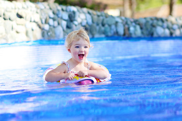 Little girl having fun in swimming pool