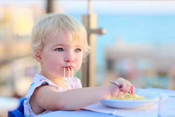 Cute toddler girl eating pasta in restaurant