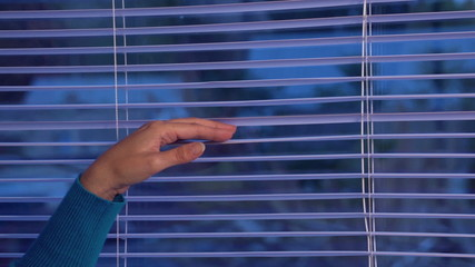 girl opens the blinds and looks out the window