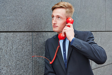Man making call with red phone on wall