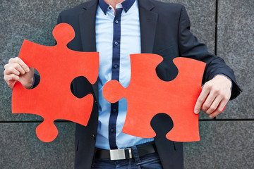 Business man holding red jigsaw puzzle pieces