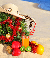 Christmas tree with woman beach hat, fresh juice and ripe fruits