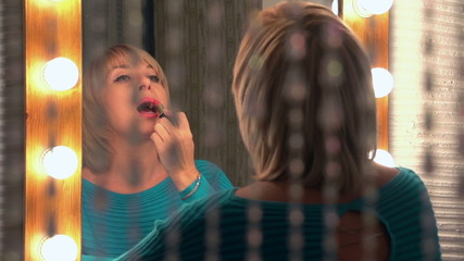 beautiful woman paints her lips, slow motion, dolly 1