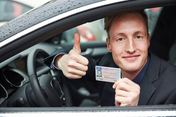 Young man holding drivers licence and thumps up