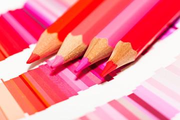 crayons de couleurs rouge rose orange sur un nuancier de teintes