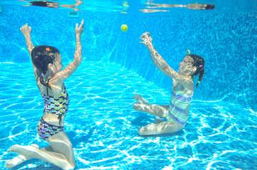Kids swim in pool underwater, children on vacation