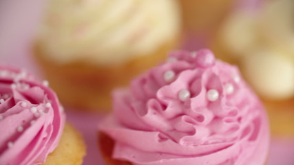 Closeup pan of beautifully decorated pink and white cupcakes