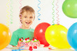 Little smiling kid with a birthday cake and balloons