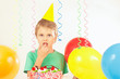 Little kid in holiday hat with a birthday cake and balloons