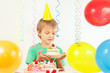 Young boy in festive hat with a piece of birthday cake