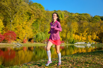 Woman running in autumn park, girl runner jogging outdoors