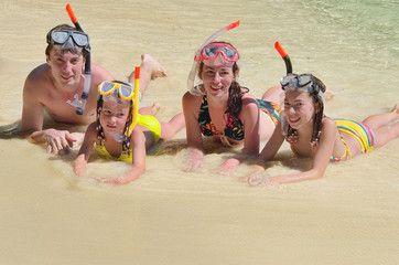 Family in snorkels on tropical beach having fun on vacation