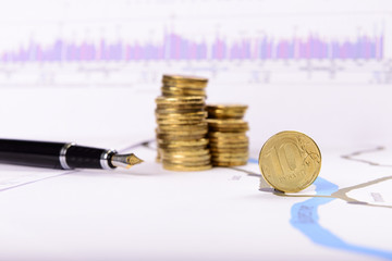 pen and coins on the background of graphs and charts