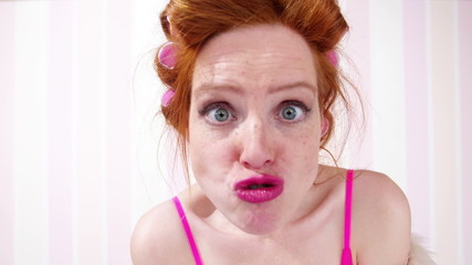 Young Redhead Woman Curlers In Hair Pulling A Face