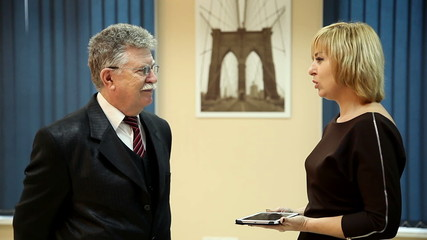 beautiful woman and elderly businessman talking in the office