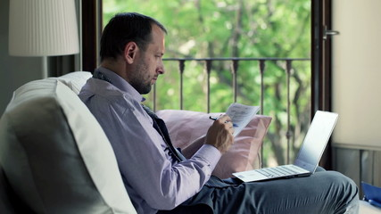Handsome businessman working with laptop and documents on sofa a