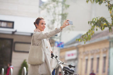 Beautiful young woman taking a self portrait on the street