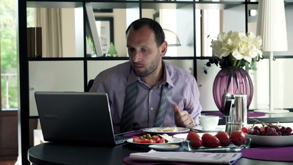 Young businessman working with laptop during breakfast by the ta