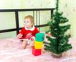 Довольный малыш в костюме деда мороза построил башню из кубиков
