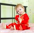 Годовалый ребенок говорит по телефону в новогоднем костюме