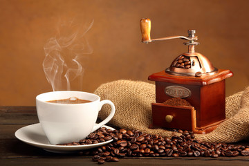 Black coffee in white cup with smoke and coffee grinder