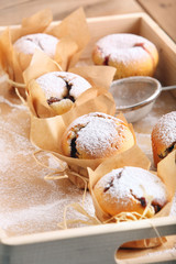Muffins with jam sprinkled with powdered sugar on wooden tray