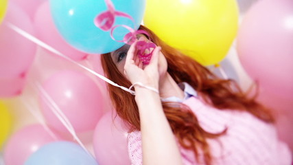 Young woman blows streamers in slow motion with balloons
