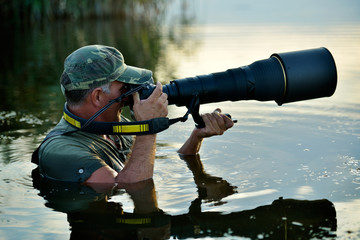 wildlife photographer outdoor, standing in the water